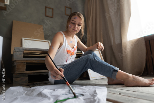 Valokuvatapetti a girl student artist sits on the floor in an art studio holding a brush in her hands and draws on a crumpled piece of paper