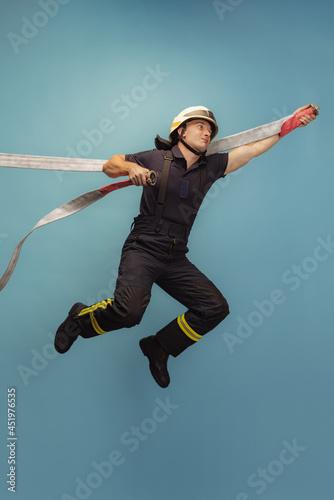 Photo Vertical portrait of young male fireman in uniform posing with water hose over blue background