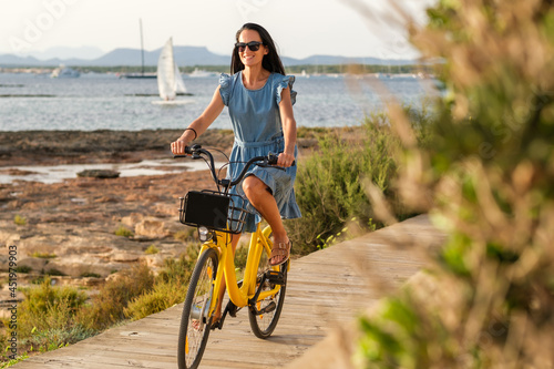 Content female in summer dress and sunglasses riding vibrant yellow bicycle alon Fototapete