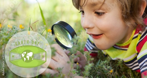Composition of green globe logo and earth day text over boy using magnifying glass in nature