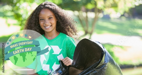 Composition of green globe logo and earth day text over smiling girl cleaning up the countryside