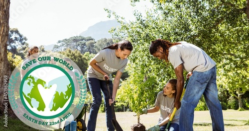 Composition of green globe logo and earth day text over volunteers planting tree in countryside