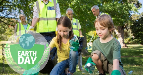 Composition of green globe logo and earth day text over volunteers cleaning up countryside