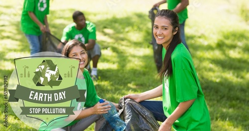 Composition of green globe logo and earth day text over smiling volunteers cleaning up countryside