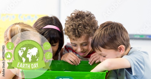 Composition of green globe logo and earth day text over children looking in recycling box