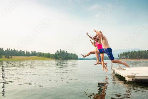 Group of kids jumping off the dock into the lake together during a fun summer vacation Fototapeta