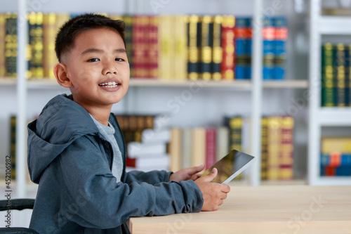 Asian boy on grey sweatshirt sit at school desk, lower head down to concentrate Fototapet