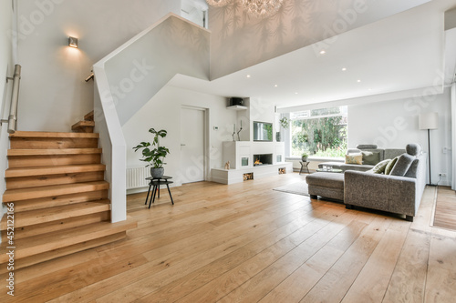 Cozy house interior with a wooden floor, large gray sofa, and stairs leading to the second floor