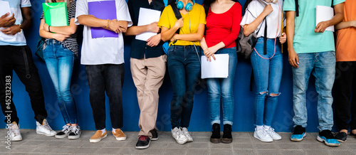 Photo Horizontal banner image of group of multiracial teenage high school students ready to go back to school standing against blue background wall