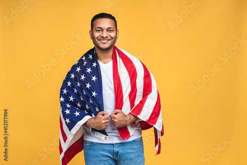 Fotografiet Photo of cheerful american african indian man protester raise american national flag black people revolution love all human beings express unity solidarity isolated over yellow background