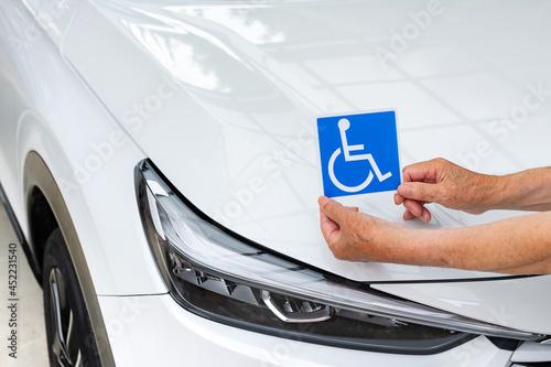 Vászonkép 車椅子マークを車体に貼る老人