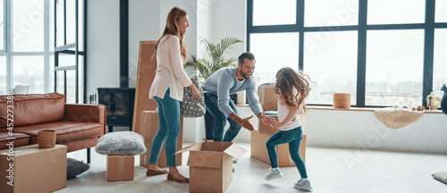 Happy young family smiling and unboxing their stuff while moving into a new apartment