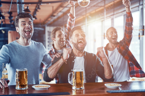 Fotografia Cheering young men in casual clothing drinking beer and watching sport game whil