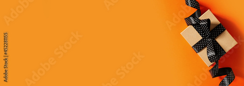 Halloween and black friday gift box with ribbon on orange background