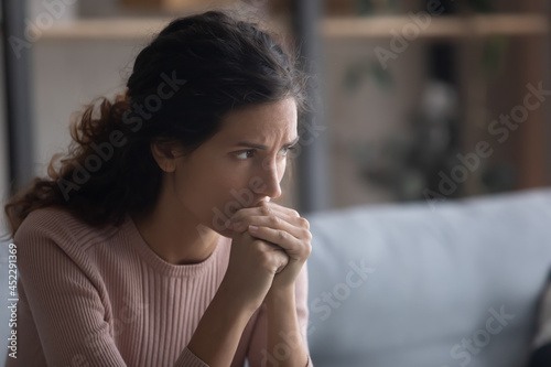 Canvas-taulu Close up upset face of young Latina woman deep in sad thoughts