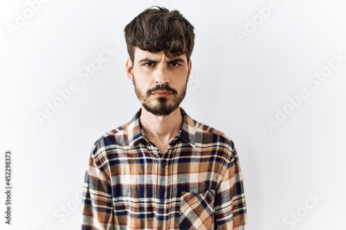 Fotografie, Obraz Hispanic man with beard standing over isolated background skeptic and nervous, frowning upset because of problem