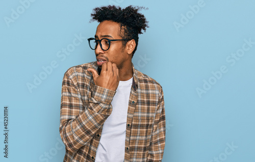 Fotografija Young african american man with beard wearing casual clothes and glasses looking stressed and nervous with hands on mouth biting nails