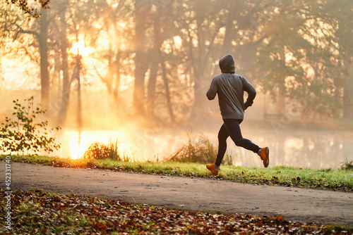 Fotografering Male runner exercising at autumn in park