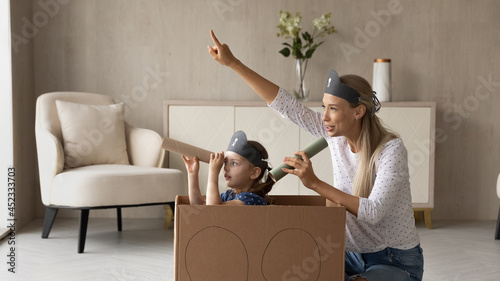 Canvas Excited kid and happy mom playing pirates at home, sailing toy carton box ship, looking forward through spyglasses