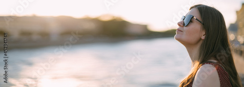 Foto Portrait of a beautiful young woman on the embankment of the river at sunset in summer