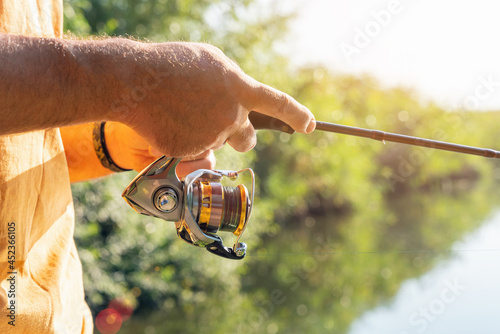 Canvastavla Spinning fishing on the river, the fisherman holds a fishing rod in his hands an