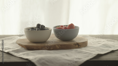 Fotografiet fresh blueberries and strawberries in ceramic bowls with natural light