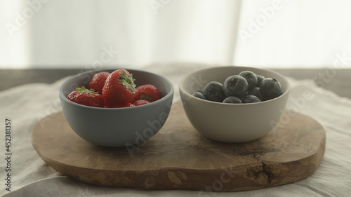 Fotografie, Tablou fresh blueberries and strawberries in ceramic bowls with natural light