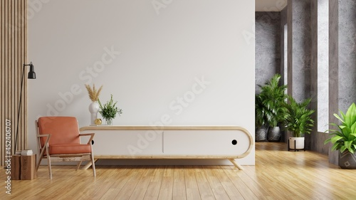 Foto Leather armchair and a wooden cabinet in living room interior with plant,White wall