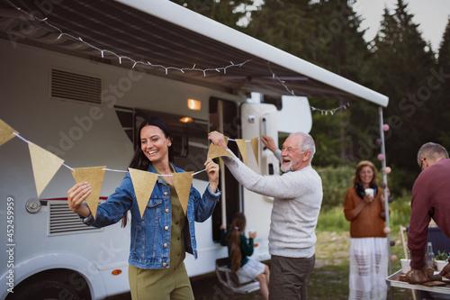 Billede på lærred Multi-generation family preparing party by car outdoors in campsite, caravan holiday trip