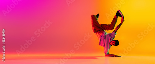Canvas-taulu Flyer with young stylish man, break dancing dancer training in casual clothes isolated over gradient pink yellow background at dance hall in neon light