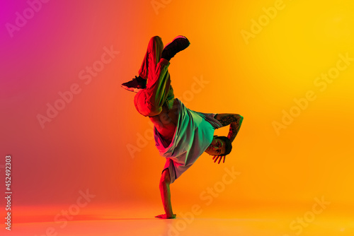 Portrait of young stylish man, break dancing dancer training in casual clothes isolated over gradient pink yellow background at dance hall in neon light Fotobehang