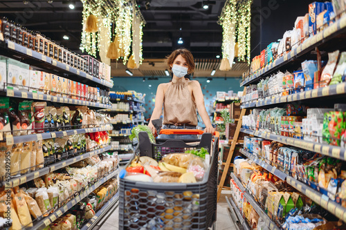 Young housewife woman 20s wearing casual clothes protective mask shopping at supermaket store with grocery cart looking camera inside hypermarket Fototapet