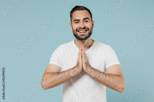 Fototapeta Young asking smiling man 20s in white t-shirt hands folded in prayer gesture, begging about something isolated on plain pastel light blue color background studio portrait