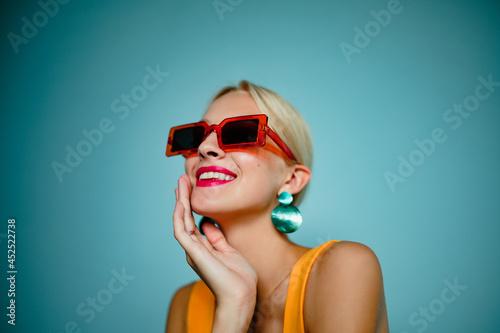 Fotografiet Happy smiling fashionable woman wearing trendy summer orange sunglasses, green shell earrings, posing on blue background