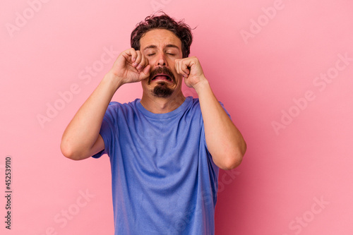 Canvas Print Young caucasian man isolated on pink background whining and crying disconsolately
