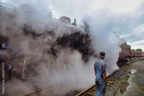 Fotografie, Obraz View of An Antique Steam Locomotive Warming Up Blowing Steam and Lots of Smoke o
