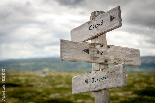 Wallpaper Mural god is love text quote on wooden signpost outdoors in nature.