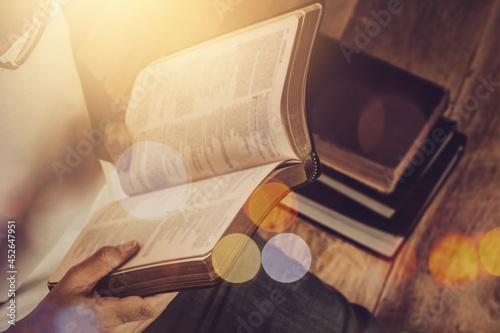 Close up of a woman hand  hold and reading the open bible, blurred page on woode Fototapeta