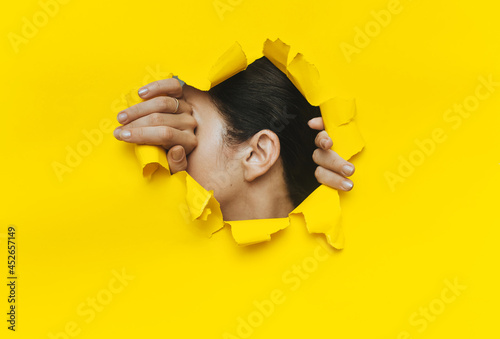 Close-up of a woman's ear and hands through a torn hole in the paper Fototapet