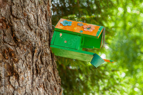 Foto Beautiful green birdhouse on a tree trunk in the park or forest