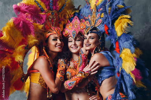 Photographie Three Woman in brazilian samba carnival costume with colorful feathers plumage
