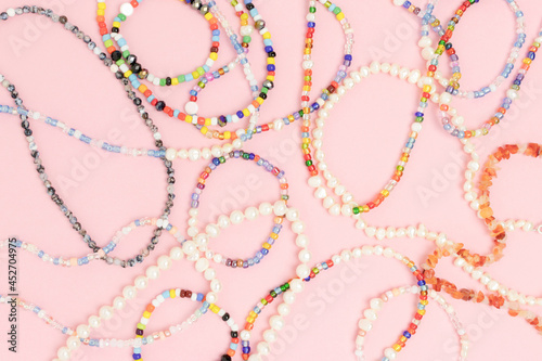 Necklaces and bracelets made from multicolored beads and pearls on a pink pastel background Poster Mural XXL
