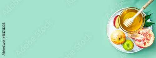 Obraz na plátně Honey, apple and pomegranate on a mint-green background