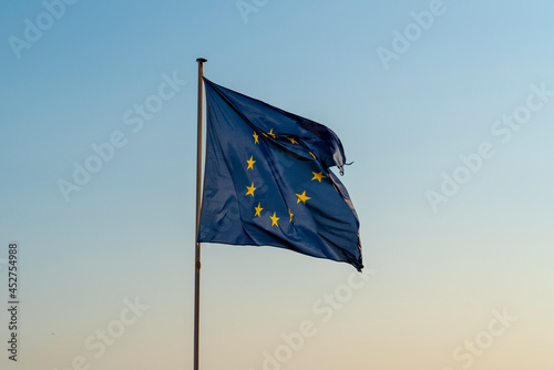 Fototapeta The European Union flag flies in the wind at sunset and a cloudless sky