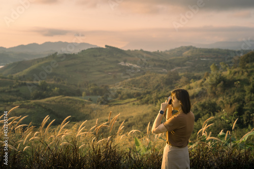 Fotografie, Obraz solo woman travel take photo and sightseeing sunrise on mountain at thailand