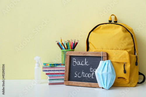 Chalkboard with text BACK TO SCHOOL, set of stationery and medical mask on color background
