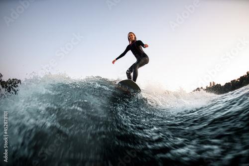 athletic female wakesurfer balanced on the board on river wave Fototapeta