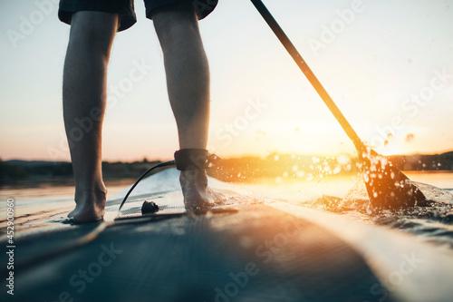 Close up of man paddleboarding at sunset Fotobehang