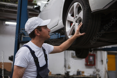 Fotografiet Male car service worker examining wheels of a car on the lift