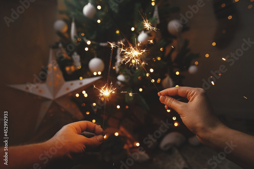 Hands holding burning sparklers on background of christmas tree and glowing star in festive scandinavian room Fototapet